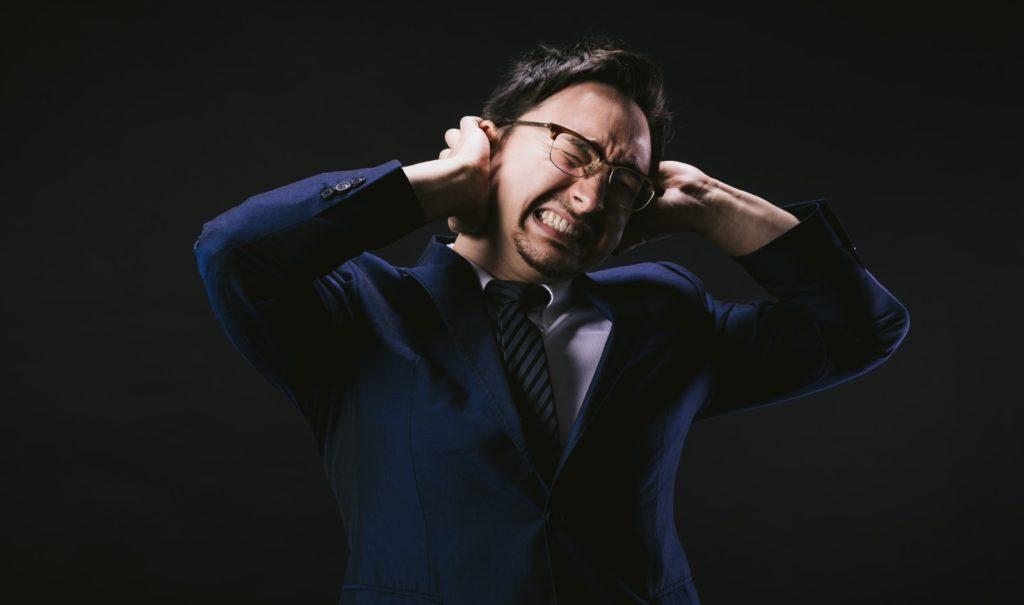 両耳を塞ぐ男性の画像