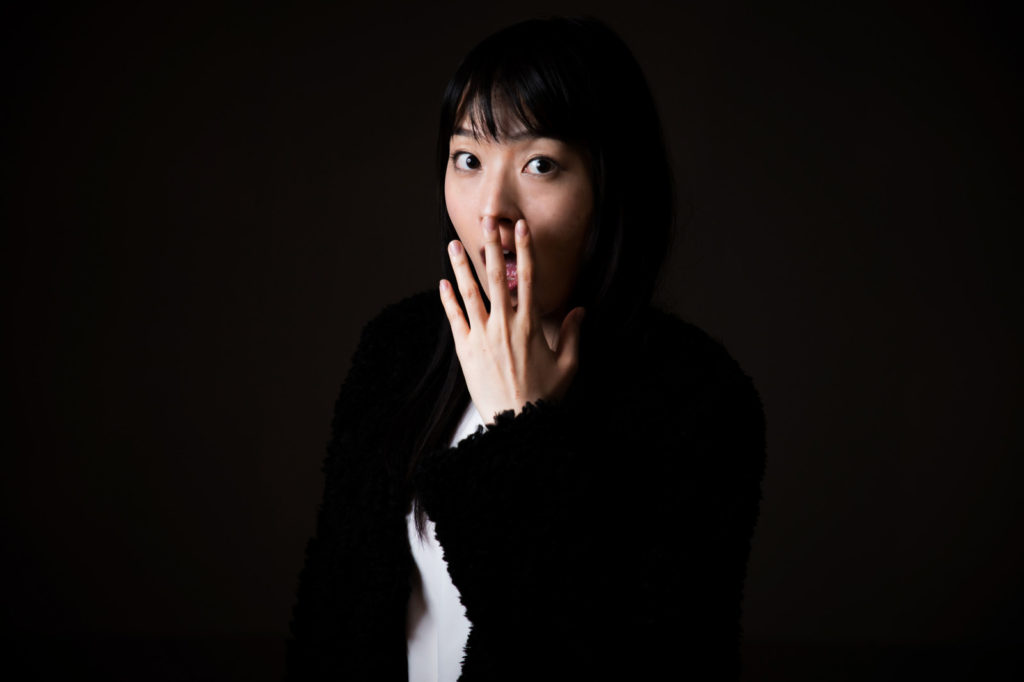 手を口元にあてヒヤッとする女性の画像