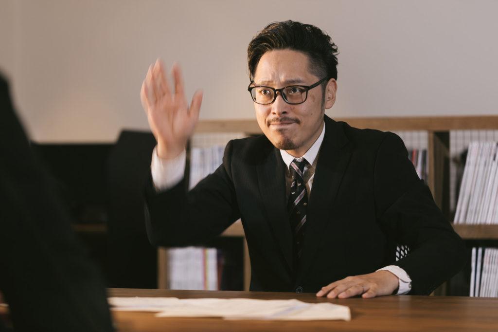 質問するために挙手をする男性の画像