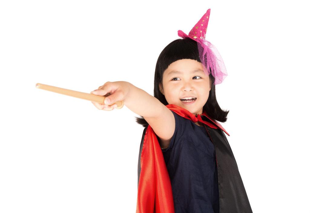 笑顔で魔法の杖を突きだす少女の画像