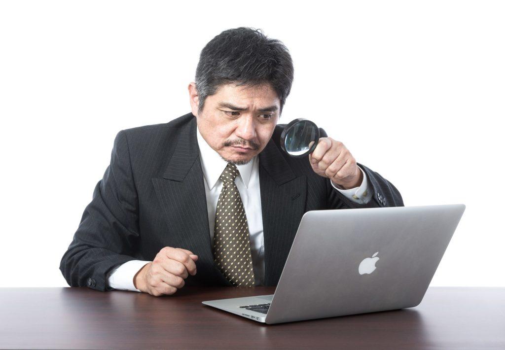 虫メガネでパソコンをのぞき込む男性の画像