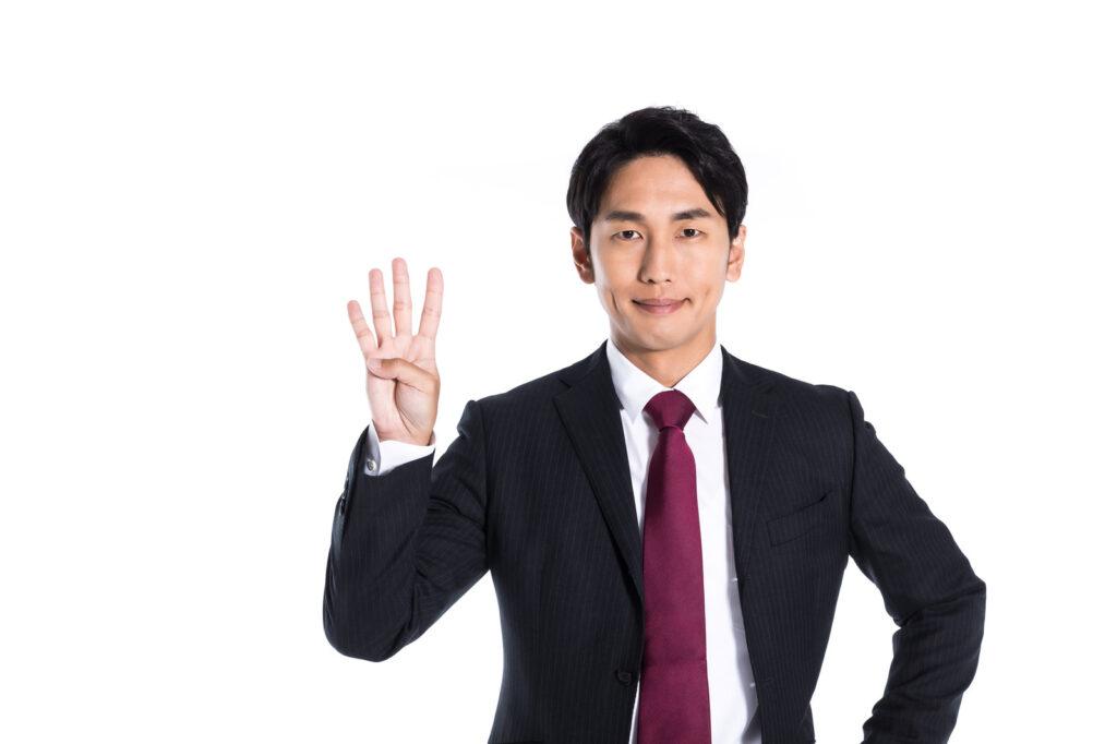 指を四本立てている男性の画像